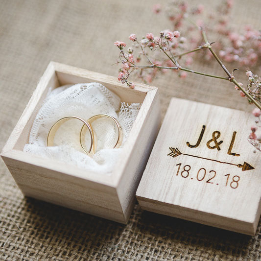 Wedding rings in wooden box with laser engraving